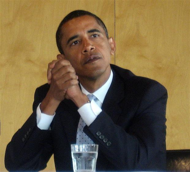 Obama with elbows on table clasping his hands together looking pensive
