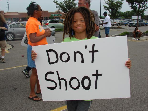 Boy holds sign that says Don't Shoot
