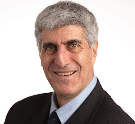 Head shot of gray haired smiling man in dark suit