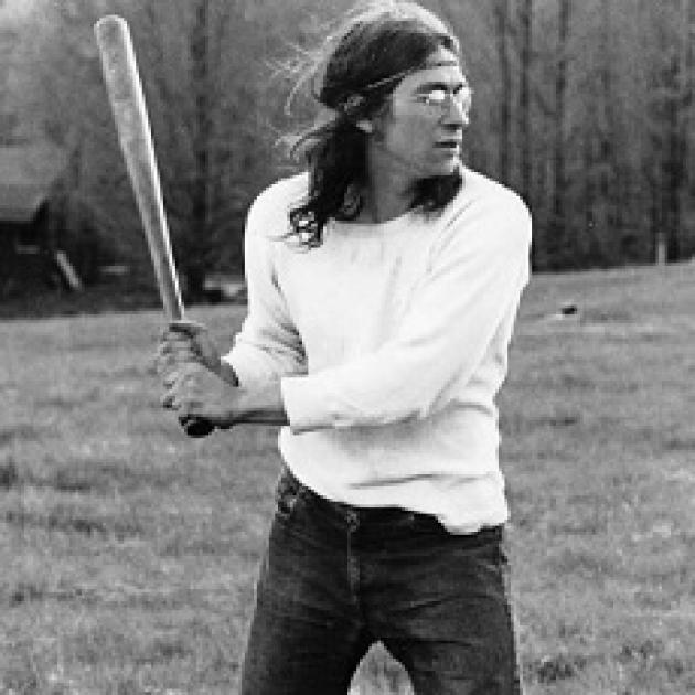 Black and white photo of a young man with long flowing brown hair with a headband across his forehead holding a baseball bat as if he's about to swing