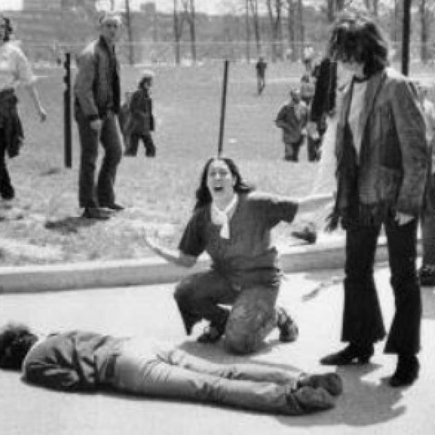 Man lying on the ground dead a woman screaming over his body, others looking on