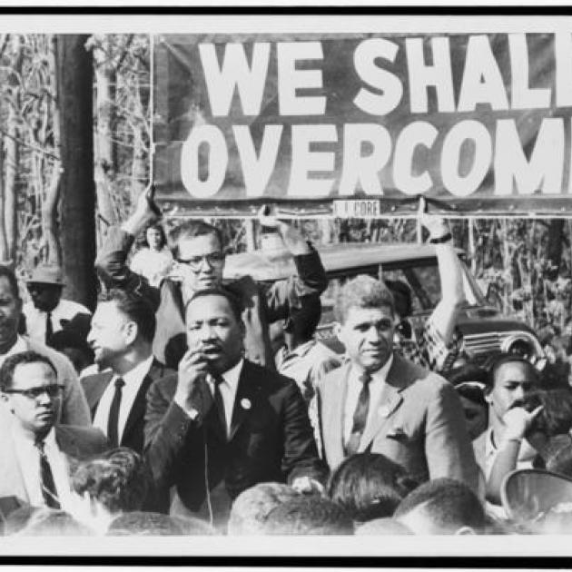 Black and white photo of Martin Luther King Jr. and others marching under sign that says We Shall Overcome