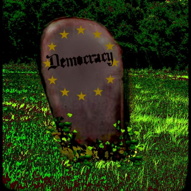Tombstone that says Democracy on it in a grassy field