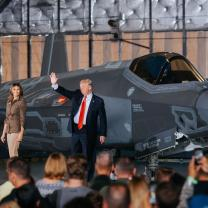 Trump, heavyset man in suit with red tie waving next to wife Melania, shapely woman with long brown hair standing in front of a military plane with people in foreground facing him