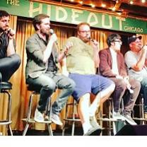 Different sizes and types of white guys sitting on stools on a stage, a couple talking into mics