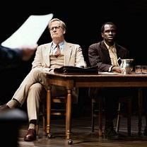 White man and black man sitting at a table looking very solemn