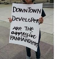 Sign being held outside reading Downtown developers are the aggressive panhandlers