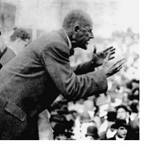 Black & white photo of a thin bald man sideways speaking and gesturing with arms outstretched to a crowd of people