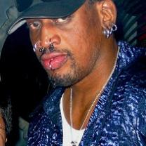 Black man in a baseball cap with lots of facial rings in lips, nose and ears wearing a blue shirt