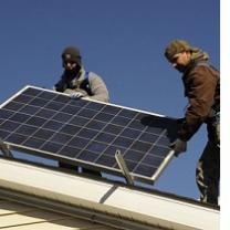 Two guys on a roof installing a solar panel