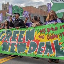 Banner that says Green New Deal and people marching