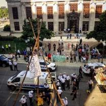 Crowd of protestors outside a big government building with a tripod looking wooden structure in the street