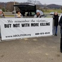 People outside holding a long white banner with black letters saying We remember the victims...But not with more killing and www.abolition.org and a phone number