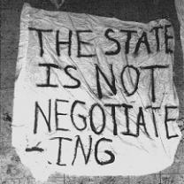 A crudely hand lettered sign on what looks like a sheet saying The state is not negotiating
