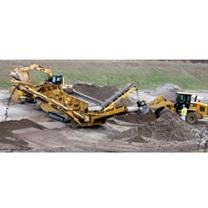 Big yellow construction machine digging into the soil