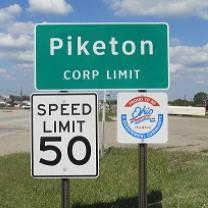 Green road sign saying Piketon Corp Limit, another sign saying Speed Limit 50 and a sign with an Ohio logo on it and in the background a highway and some grass and the blue sky with white clouds