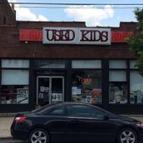 Brick building with sign at top saying Used Kids and a storefront with windows, a black car parked in front