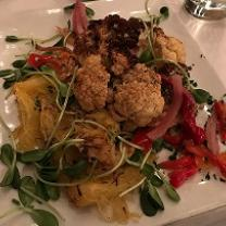 A white square plate on a table filled with greens, little toasty looking brownish balls, squash and red slivers of food