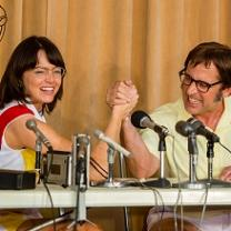 Young woman with short dark hair and glasses at a podium with microphones arm wrestling a middle aged man with brown hair and glasses.