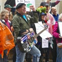 Guy with cap and guitar covered with stickers with his fist in the air in front of a crowd of people