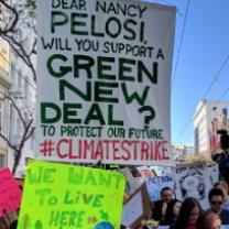 Outdoor rally with signs, one says We Want to Live Here, one says Dear Nancy Pelosi will you support a Green New Deal