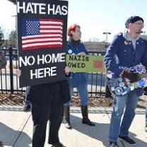 Someone holding a sign with a US flag on it on black background saying Hate has no home here, a guy playing a guitar that's covered with stickers with political sayings and a woman with red hair behind in the middle with a sign against Nazis