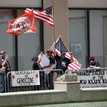 Guys waving flags and with Ku Klux Klan signs