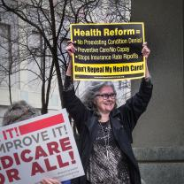 Gray haired woman holding protest sign above head asking for Health Reform