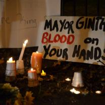 "Candles and a sign that says ""Mayor Ginther Blood on your hands"""
