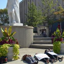 Student lying on ground beneath Columbus statue
