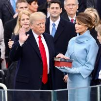 Donald Trump frowning with hand on Bible at swearing in ceremony