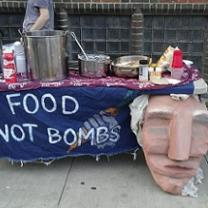 Big paper mache face hanging on the front of a table outside next to a blue sign with white hand drawn letters that say Food Not Bombs and a lot of pots and pans and condiments on the table and a brick wall in the background