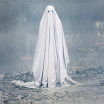Person in a white sheet with two eye holes against an eerie gray background