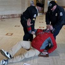 Man being dragged across the floor by two uniformed policemen