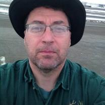 Man with glasses and wide brimmed black hat, looking grim