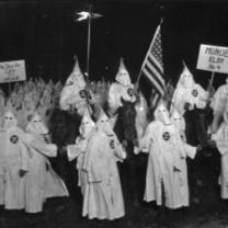 People in white robes with pointy top hats in a circle outside at night with a flag