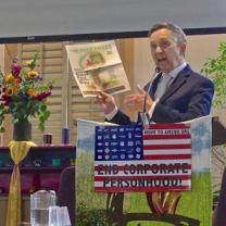 Dennis Kucinich, 60-ish white guy in a suit at a podium holding up a copy of the Free Press