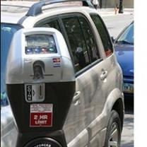 Close up of a parking meter and cars parked behind it
