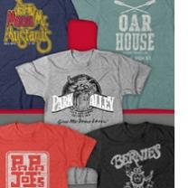 Five T-shirts laying out flat each with a different logo from a campus bar on it