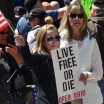 Woman holding sign saying Live Free or Die