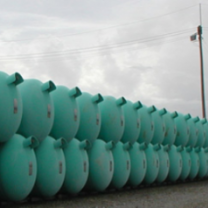 Dozens of blue green barrels lined up