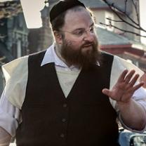 Large white man with jewish hat and wire rimmed glasses, a longish brown beard wearing a white collared button down shirt and black button vest his hand gesturing as he talks to someone to his right