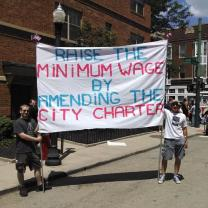 Two men holding sign reading Raise the MInimum wage by amending the city charter