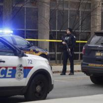 Police car and officer with gun outside building with crime tape around it