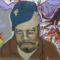 A black man wearing a blue baseball cap looking sad