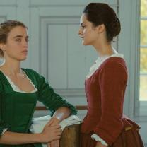 Two women in Victorian-looking dresses