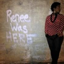 The words Renee was HERE spray painted on a brown wall and a black woman with short hair and a red and white shirt with a black necklace and black pants stands against the wall looking to the right