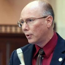 Balding white guy with sire rimmed glasses, a blue suit coat and maroon shirt and striped tie holding a silver microphone talking into it