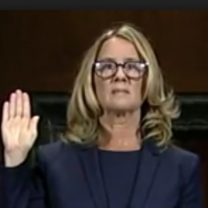 Blonde woman with glasses holding her hand up as if swearing to tell the truth