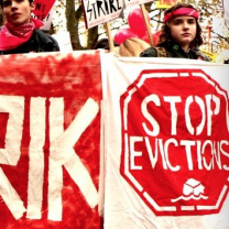 People holding signs saying Stop Evictions